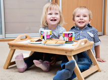 Funny children are eating dessert. Funny children are sitting on a floor and are eating dessert Royalty Free Stock Photography