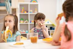 Funny children eating healthy food. Kids lunch at daycare or kindergarten stock image