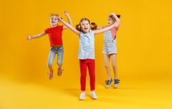 Funny children girls jumping on colored yellow background Stock Images