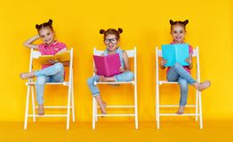 Funny children girls read books on a colored yellow background. Funny children girls read books on colored yellow background royalty free stock image