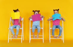 Funny children girls read books on colored yellow background. Funny children girls read books on a colored yellow background royalty free stock photos