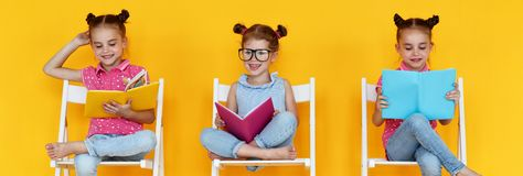 Funny children girls read books on a colored yellow background Royalty Free Stock Image