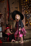 Funny children girls in witch costume play for Halloween   dark Royalty Free Stock Images