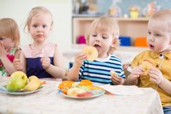 Funny children group eating fruits in kindergarten dinning room royalty free stock photography