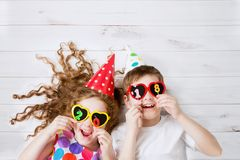 Funny children hold 2018 shaped candles. Funny children with sunglasses, hold 2018 candles, lies on the wooden floor Stock Photos