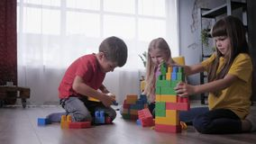 Funny children are passionate about playing constructor play and collect toys from colored parts and blocks for speed