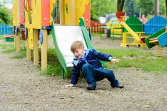 Funny children play on a children`s playground stock images