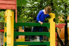 Funny children play on a children`s playground stock image