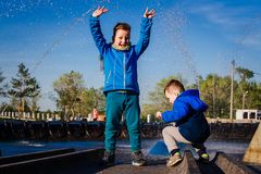 Funny children play in the fountain royalty free stock photos