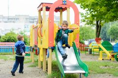 Funny children play on a children`s playground. Beautiful Ukrainian boys run on a playground and descend from the hills Royalty Free Stock Image