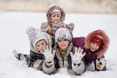 Funny children playing and laughing on snowy winter park. Happy sisters royalty free stock photography