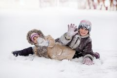 Funny children playing and laughing on snowy winter park. Happy sisters royalty free stock photos