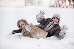 Funny children playing and laughing on snowy winter park. Happy sisters stock image