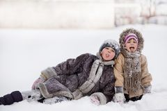 Funny children playing and laughing on snowy winter park. Happy sisters stock photography