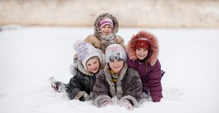 Funny children playing and laughing on snowy winter park. Happy sisters stock photo