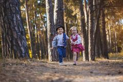 Funny kids playing in the park. Funny children are playing in the park. A boy and a girl. Carefree childhood Stock Photos