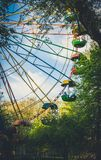 Old attraction. Ferris wheel in the old spring park. Funny children`s spring attraction. Colorful old-fashioned Ferris wheel viewed against a green park and blue Royalty Free Stock Photography