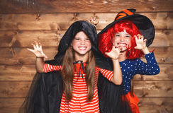 Funny children sister twins girl in witch costume in halloween. Laughing funny children sister twins girl in a witch costume in halloween stock image