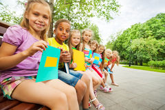 Funny children sit close on bench with books Stock Image
