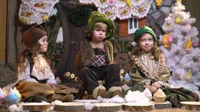 Offended boy and two girls in old festive clothes are sitting in a room with New Year decorations in the form of a. Funny children are sitting in a room with stock footage