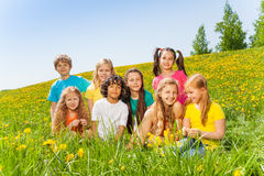 Funny children sitting together on green grass royalty free stock photo