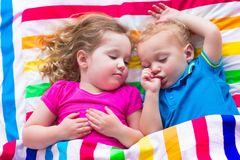 Funny children sleeping under colorful blanket Stock Photo