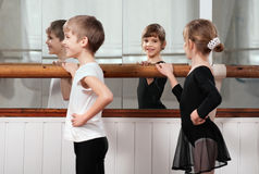 Children standing at ballet barre Stock Images