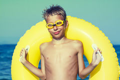 Funny chilld with swimmer goggles standing on beach enjoying summer vacation Stock Images