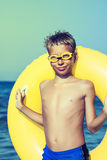 Funny chilld with swimmer goggles standing on beach Royalty Free Stock Photos