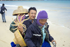 Funny Chinese fishermen on the motorcycle in Troy. China province Senjou on Hainan island beach at the Sheraton royalty free stock photography