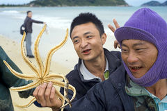 Funny Chinese fishermen on the motorcycle in Troy. China province Senjou on Hainan island beach at the Sheraton stock photo
