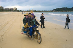 Funny Chinese fishermen on the motorcycle in Troy. China Province of Senjou on Hainan island the beach at the Sheraton royalty free stock photography