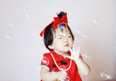 Funny Chinese little baby in red cheongsam play soap bubbles Stock Photo
