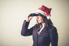 Funny christmas businesswoman with binoculars Royalty Free Stock Image