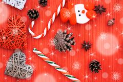 Funny Christmas composition with pine cones, lollipop, acorn, star anise, snowman and decorative hearts on a wooden background . stock photos