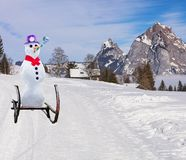 Funny christmas concept of a party snowman wearing a hat and roller tongue sliding down the ski hill slope on a sleigh stock photos