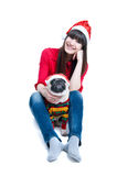 Funny Christmas dog. Funny and cute friends pretty girl and her pug dog pet wearing red Santa Claus caps, having fun, smiling with toothy smiles, dog being Stock Images