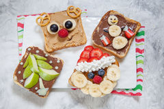 Funny Christmas faces toasts with banana, strawberry and blueberry Stock Photo