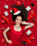 Funny Christmas Girl with Candy Cane surrounded by Presents. Beautiful expressive woman in sweet Christmas fantasy portrait with lollipop and gifts Stock Images