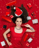 Funny Christmas Girl with Candy Cane surrounded by Presents. Beautiful expressive woman in sweet Christmas fantasy portrait with lollipop and gifts Royalty Free Stock Photography