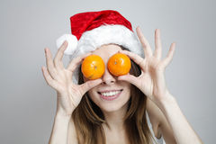 Funny christmas girl. Funny girl in a christmas hat with mandarins Royalty Free Stock Photos