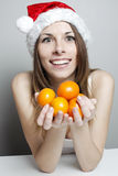 Funny christmas girl. Funny girl in a christmas hat with mandarins Stock Photo
