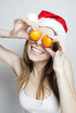 Funny christmas girl. Funny girl in a christmas hat with mandarins Royalty Free Stock Image