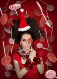 Funny Christmas Girl Holding a Candy Surrounded by Lollipops. Beautiful expressive woman in sweet Christmas fantasy portrait with lollipops Stock Image