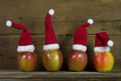 Funny christmas greeting card with four red santa hats on apple Stock Photos