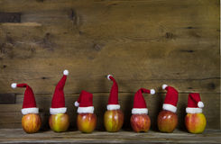 Funny christmas greeting card with seven red santa hats on apple Stock Images