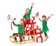 Funny Christmas Kids with Megaphone preparing New Year Gifts. Santa Claus Helpers, Cute Little Elves on Sleigh packing Christmas