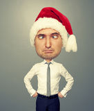 Funny christmas man in red santa hat. Over grey background Stock Photos