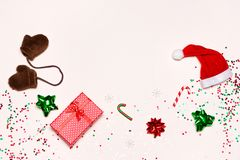 Funny Christmas and New Year background with copy space. Funny Christmas and New Year background. Wrapped gift, Santa hat, mittens, decorations and confetti stock photo