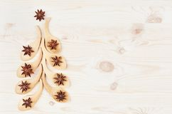Funny christmas tree of bamboo spoons with anise stars on white wood background. Royalty Free Stock Photos